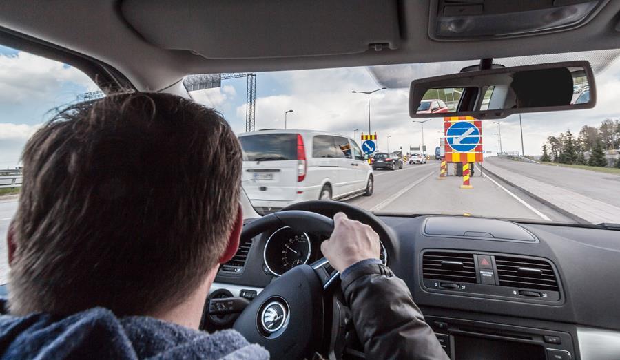 Kuvassa autoilija ajaa tietyömaa-alueelle.